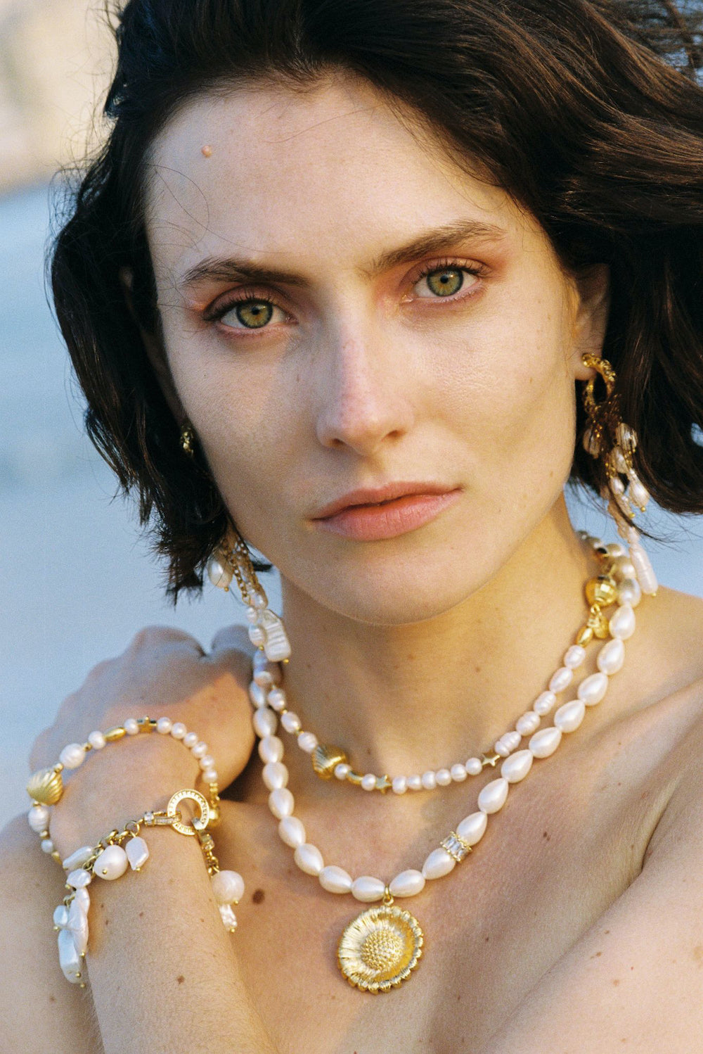 Woman wearing pearl earrings, bracelets and necklaces