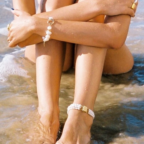 Woman sitting on the shore wearing pearl anklet and bracelet