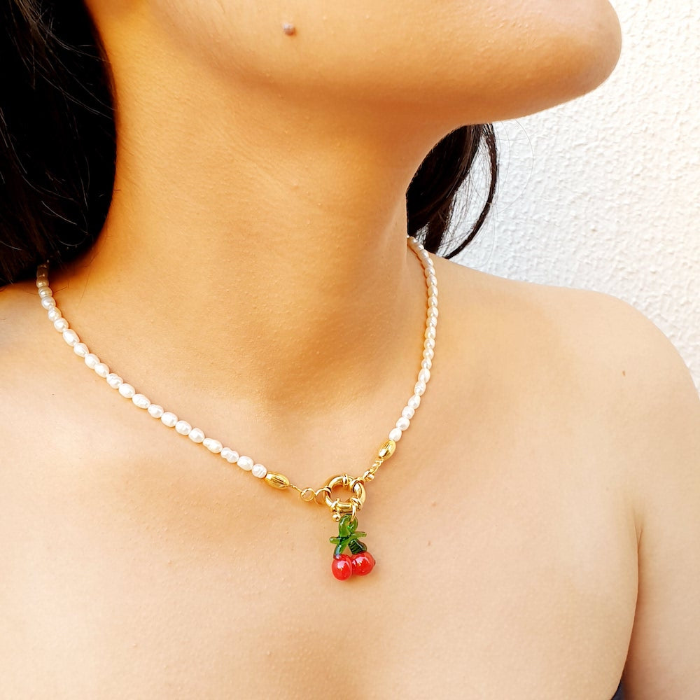 Woman wearing a short pearl necklace with a red and green Murano cherry drop pendant