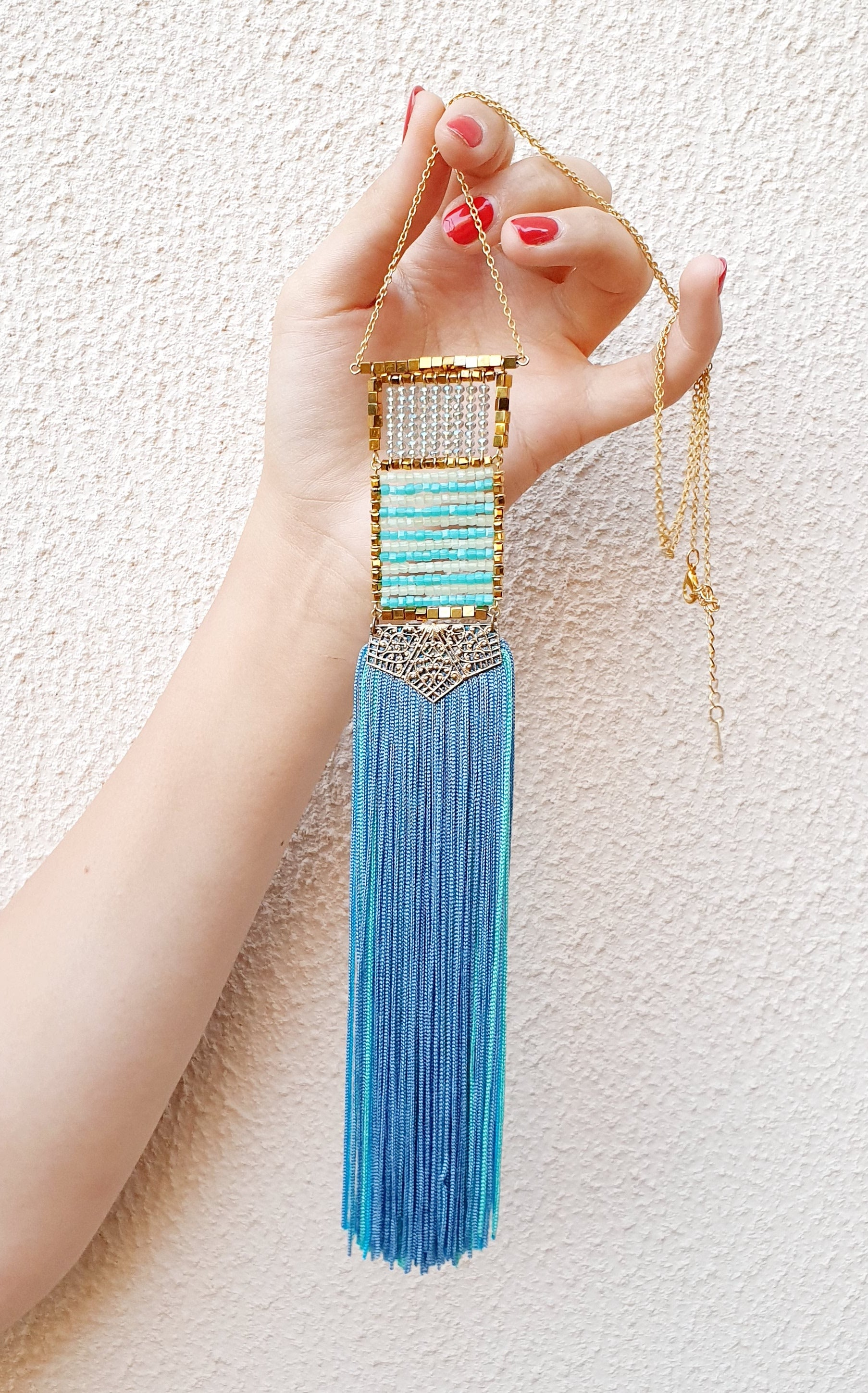 Woman's hand holding an extra long gold chain necklace with gold, clear and blue cubed crystals arranged in a a rectangular shape leading to a thick turquoise blue fringe tassels