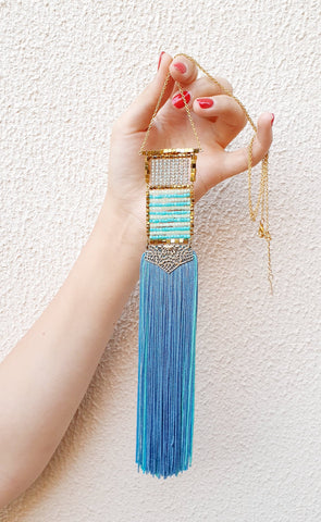 1.Hand holding necklace with rows of alternating gold, clear and turquoise blue beads in a rectangular arrangement with turquoise blue tassel fringe hanging from it