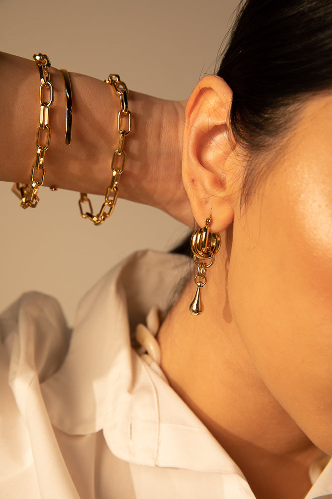 Woman wearing two gold chain link bracelets and a gold twisted mini hoop earring with detachable gold drop pendant