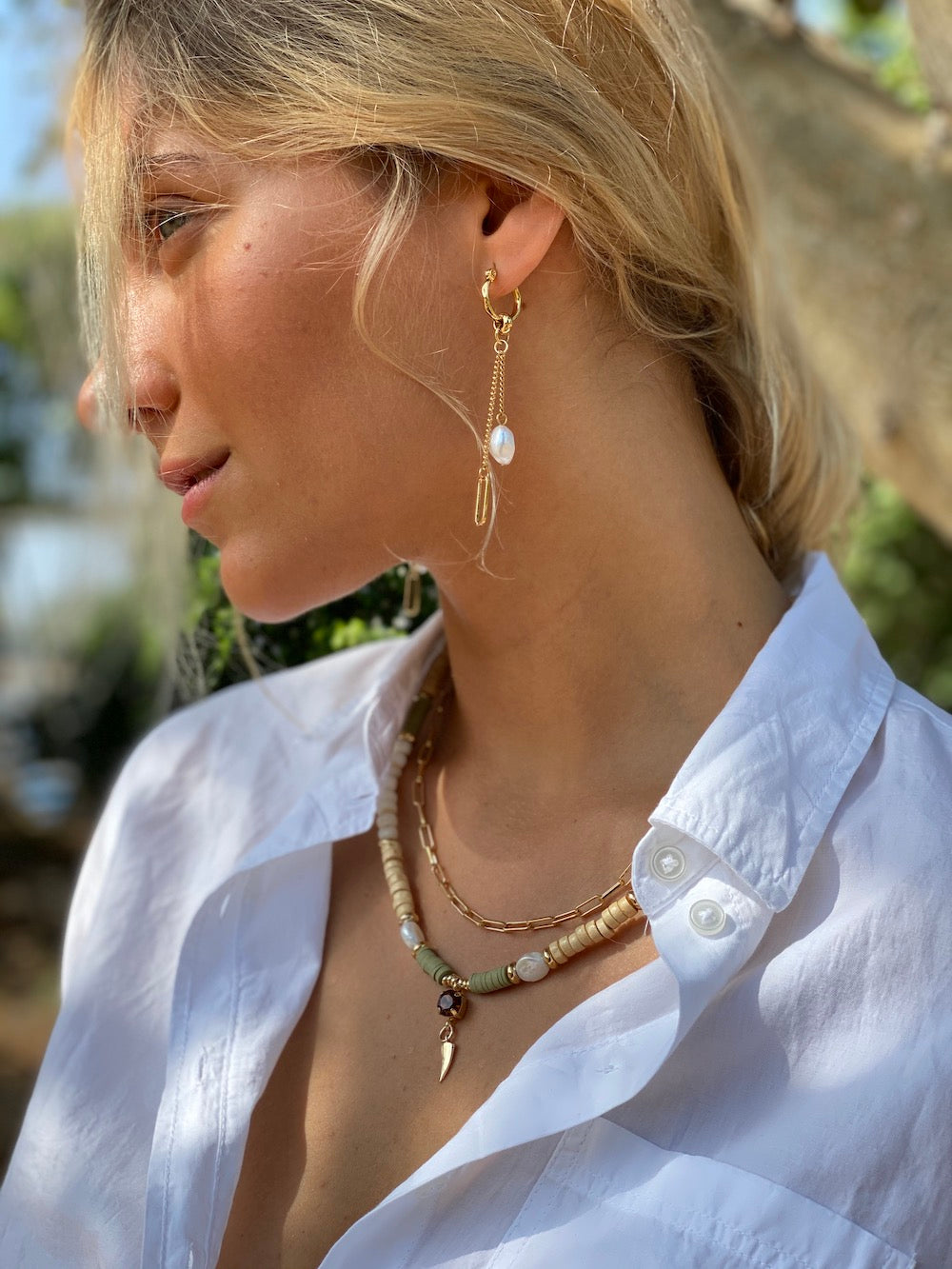 Woman wearing gold chain and pearl drop earrings with a short two layered gold chain link necklace and the second strung with shell, wood, pearl beads with a smoky brown Swarovski crystal and gold tusk pendant