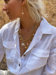 Woman in white blouse wearing Shelly Dahari three-layered necklace with gold link chains drop crystal shell pearl bead and gold charms.