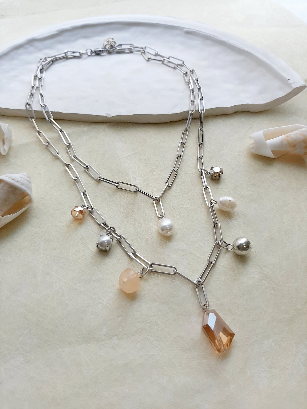 Double layered silver necklace with several drop charms made of Swarovski crystals, pearls & acrylic