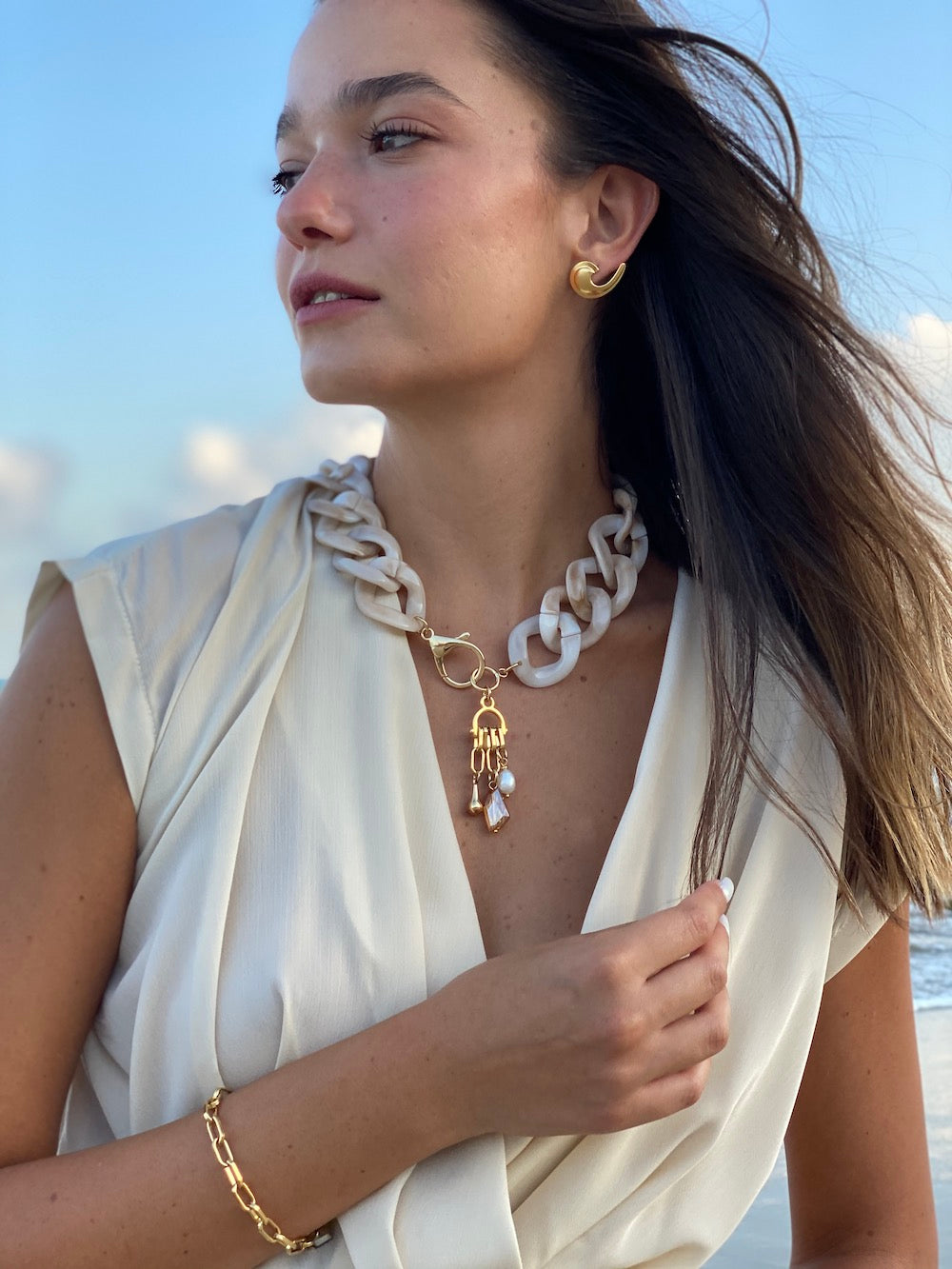 Woman outdoors wearing a short necklace made of oversized nude chain link acrylic with pearl, caramel Swarovski crystal and gold charms hanging from a gold lobster claw clasp in the front