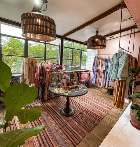 •Natural lit retail showroom with rings necklaces and earrings displayed on a central table surrounded by ethnic dresses in earthy colors