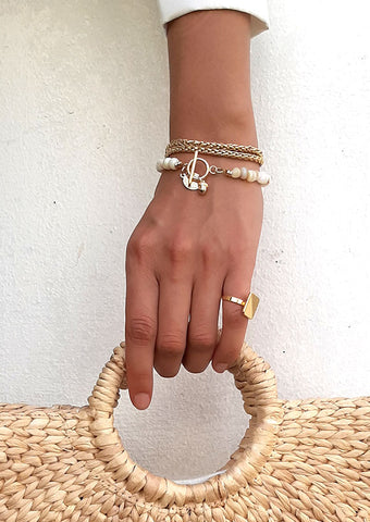 Hand holding handbag wearing gold chain bracelet beaded with shells wrapped around wrist with gold coin and acorn charms hanging from front clasp
