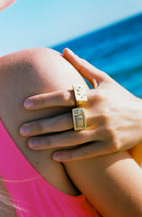 Mayol rectangle gold ring with smiley face engraving on woman's index finger at beach & rectangle gold ring with MTV logo engraving on middle finger