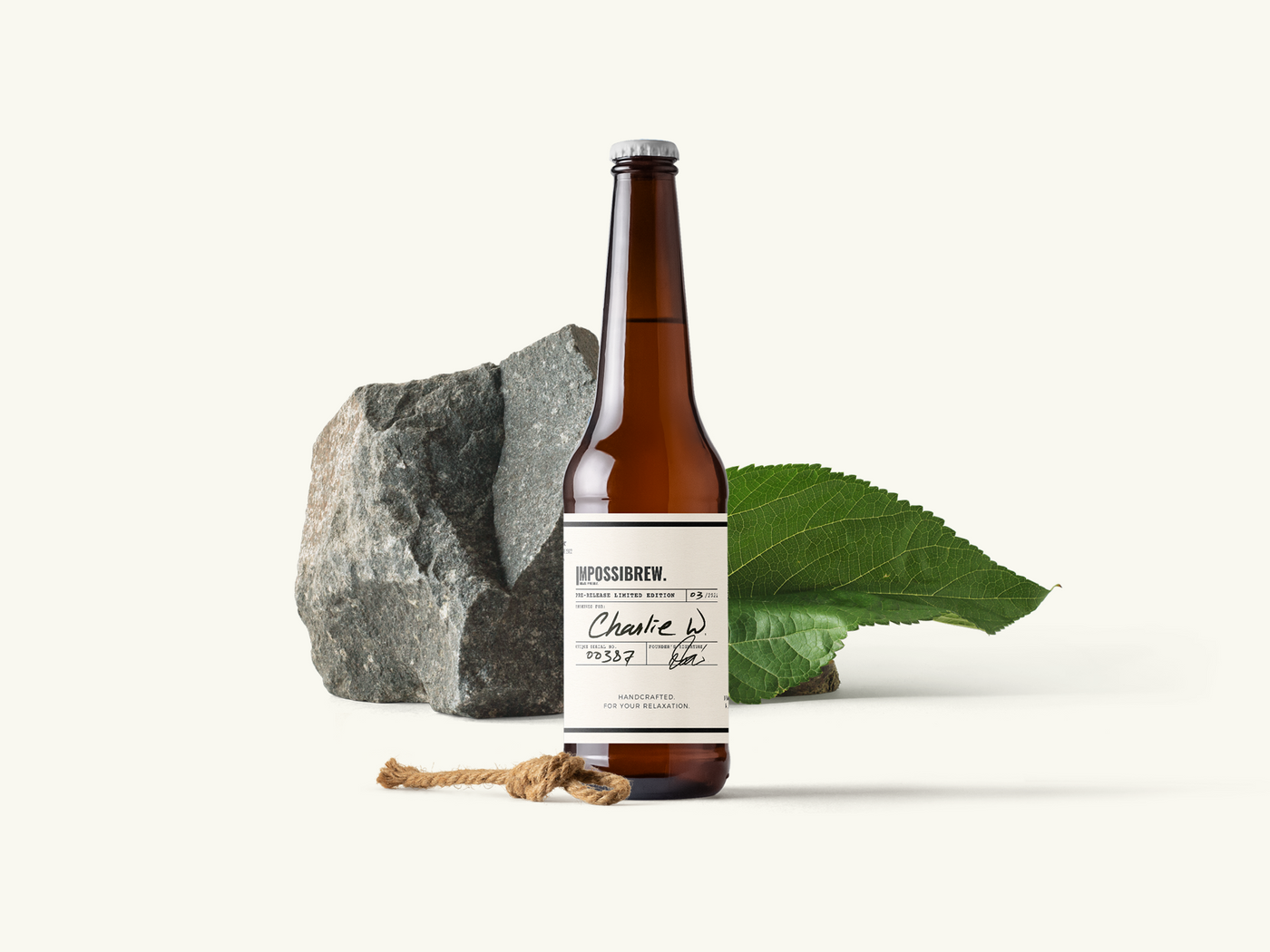 A bottle of Impossibrew theanine beer in front of natural designs, rocks and plants. highlighted and focused. studio quality. With Charlie W written on it.