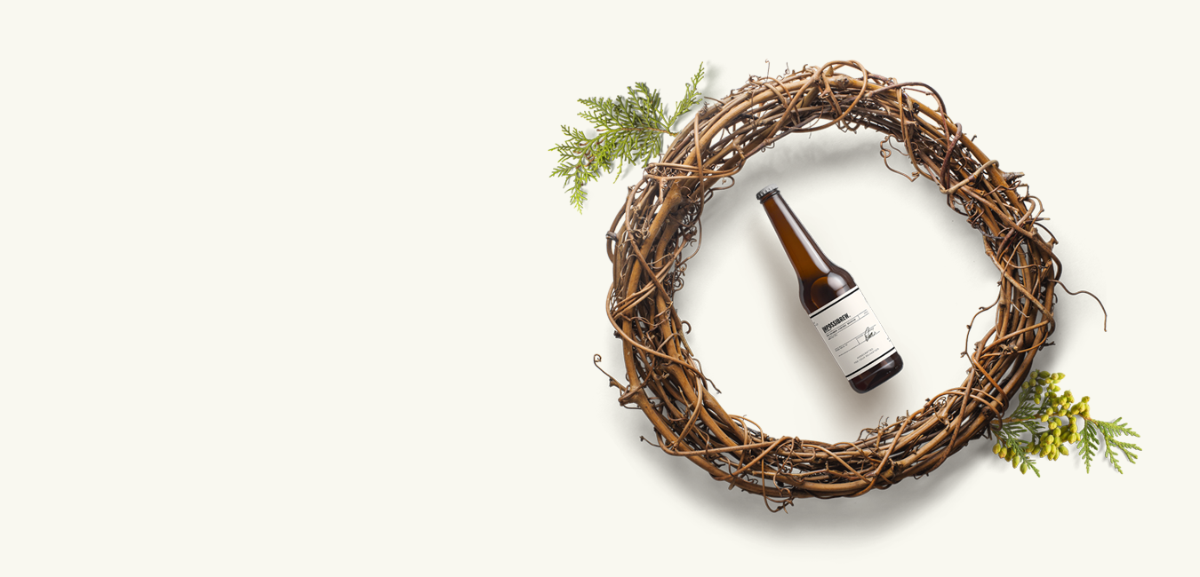 A centre focused, tilted bottle of Impossibrew theanine beer in the middle of a wreath under highlight. studio photo.