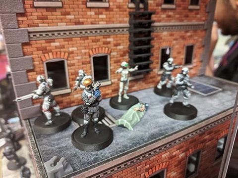 miniature soldiers gathered on a tiny, detailed brick building