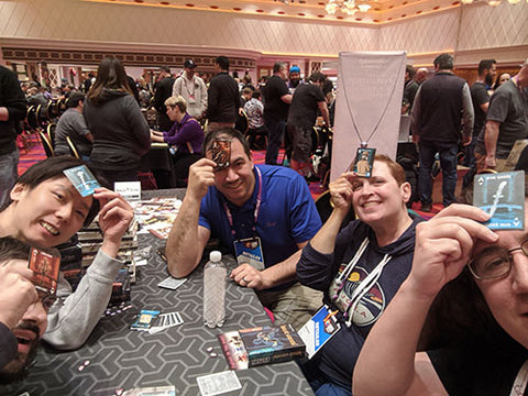 group smiling and holding cards up to their foreheads