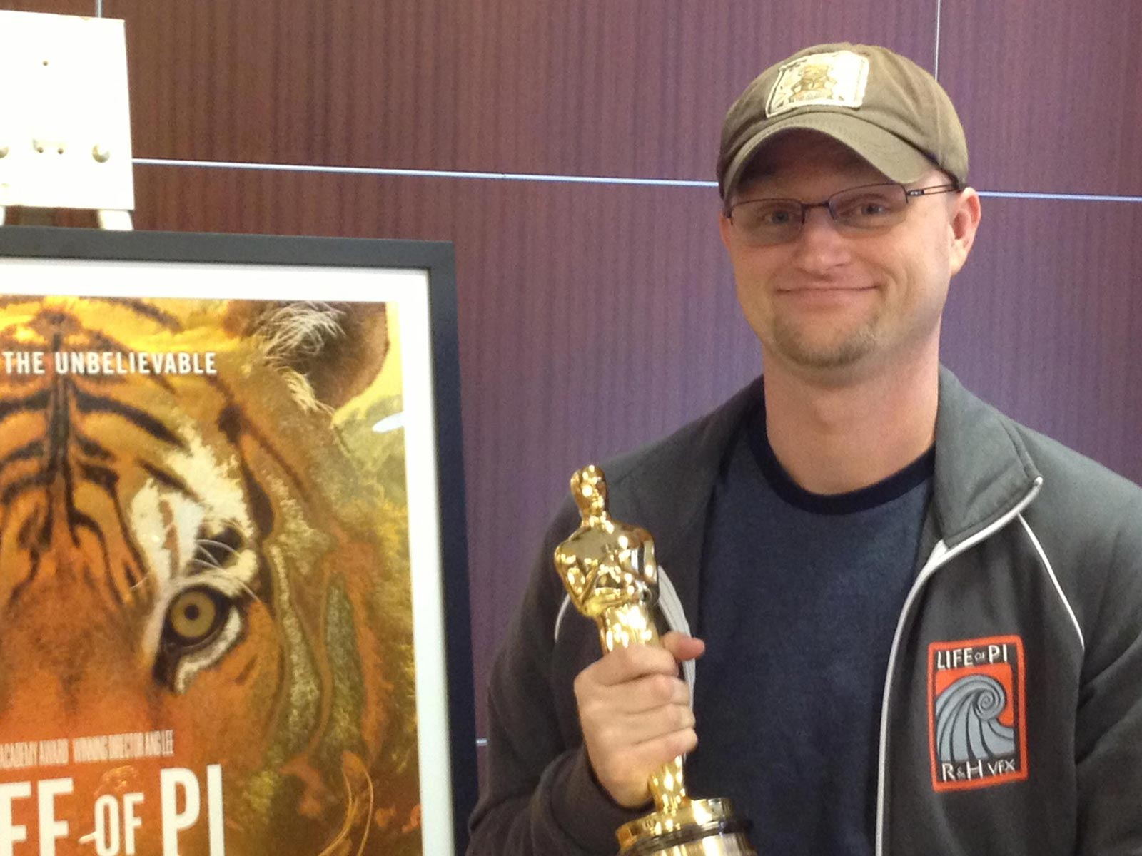 Photo of Chris holding an Oscar for his work on the movie Life of Pi
