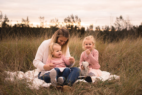 Kylie from Tribal Beach and her two little girls sitting in the grass Image Credit: Felicity Harris Photography