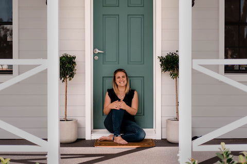 Kylie from Tribal Beach sitting in front of green door of house