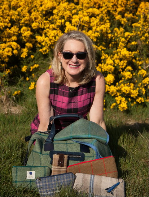 Liz Warnock posing in front of wall of flowers with J&L tweed products in front of her