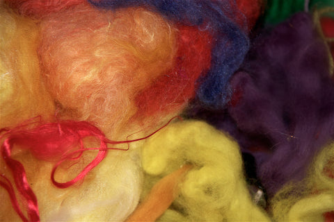 Scottish wool fabric in process of dying in colors red, yellow, purple, blue and orange