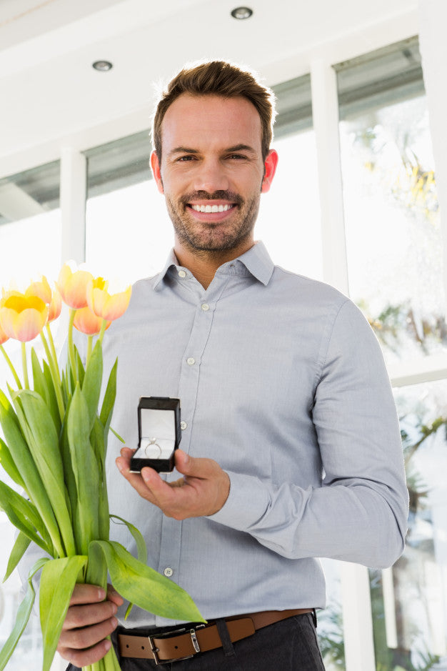 man holding a flower and a ring proposing for a marriage