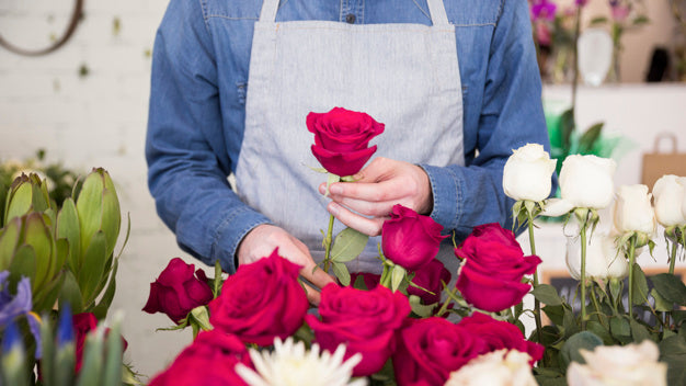 Florist presenting pink flower for grand opening