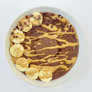 Chocolate Vanilla Cheesecake Baked Oats topped with banana and peanut butter