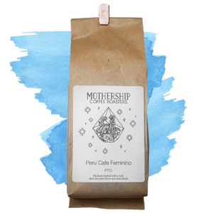 A coffee bag of Peru Cafe Femenino over blue watercolor marks