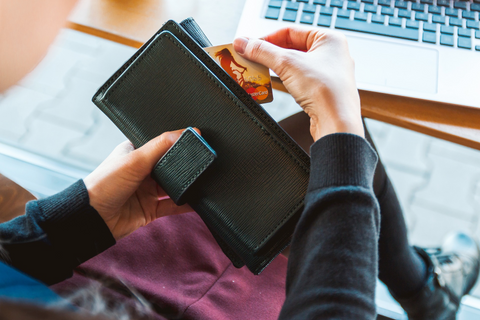 Woman taking card out of wallet