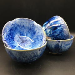 four blue and white glazed pottery bowls