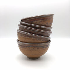 a stack of five brown ceramic bowls