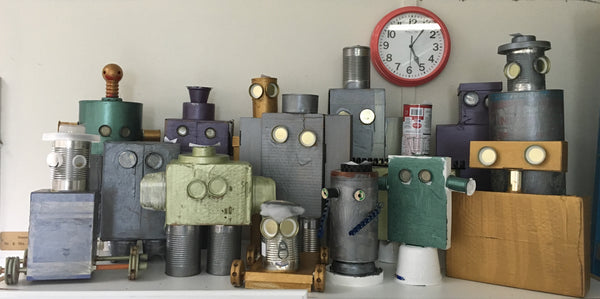 a picture of robot looking sculptures made from scrap materials such as toilet paper tubes, tin cans, bottle caps, and duct tape