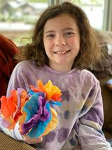 A girl holds a paper flower she made.