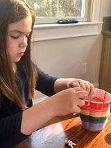 A girl weaves yarn on a cup.
