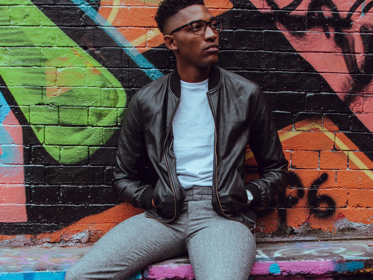 Stylish young man sitting in front of a colorful graffiti wall