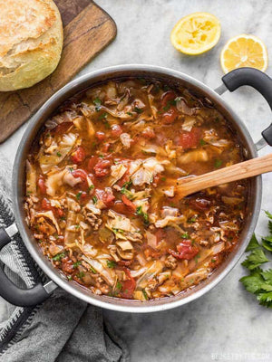 Load image into Gallery viewer, Beef and cabbage soup in the pot with a wooden spoon in the middle