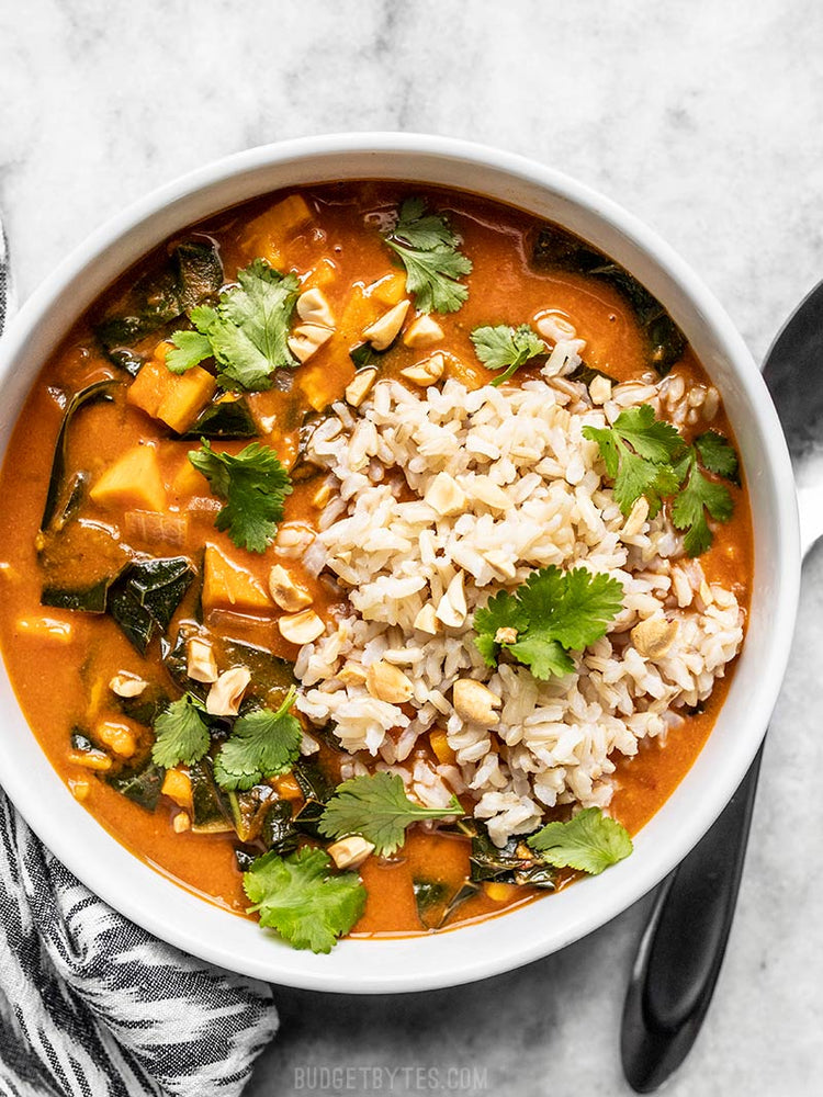 Load image into Gallery viewer, Overhead view of a bowl of west African peanut stew topped with brown rice and cilantro