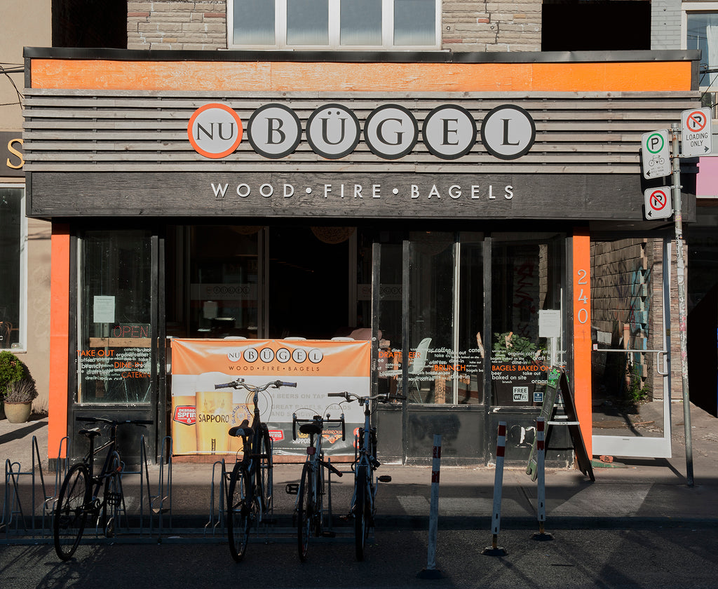 "NU Bügel storefront located in Kensington Market, Toronto. ""NU Bügel"" in black-outlined circles and the words ""Wood Fire Bagels"" below. Bike rack by the city outside the store."
