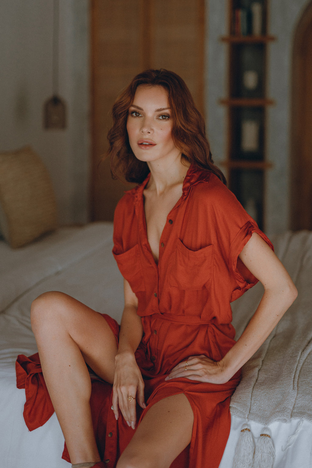 model sitting on bed wearing a red classic shirt dress