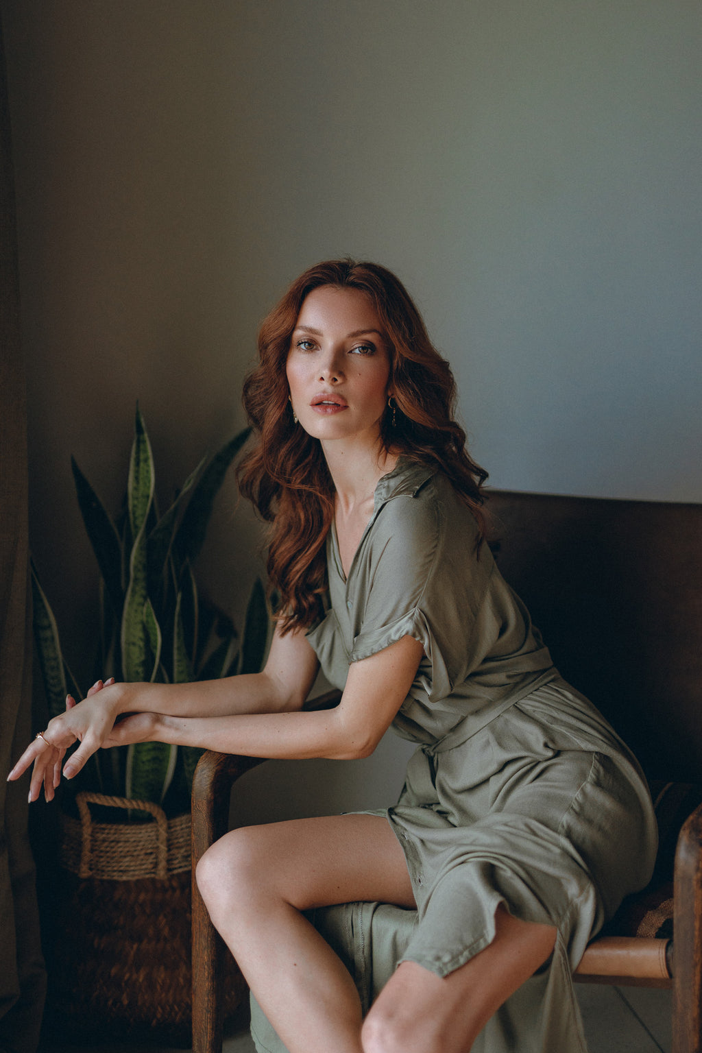 model sitting on a chair wearing olive midi dress