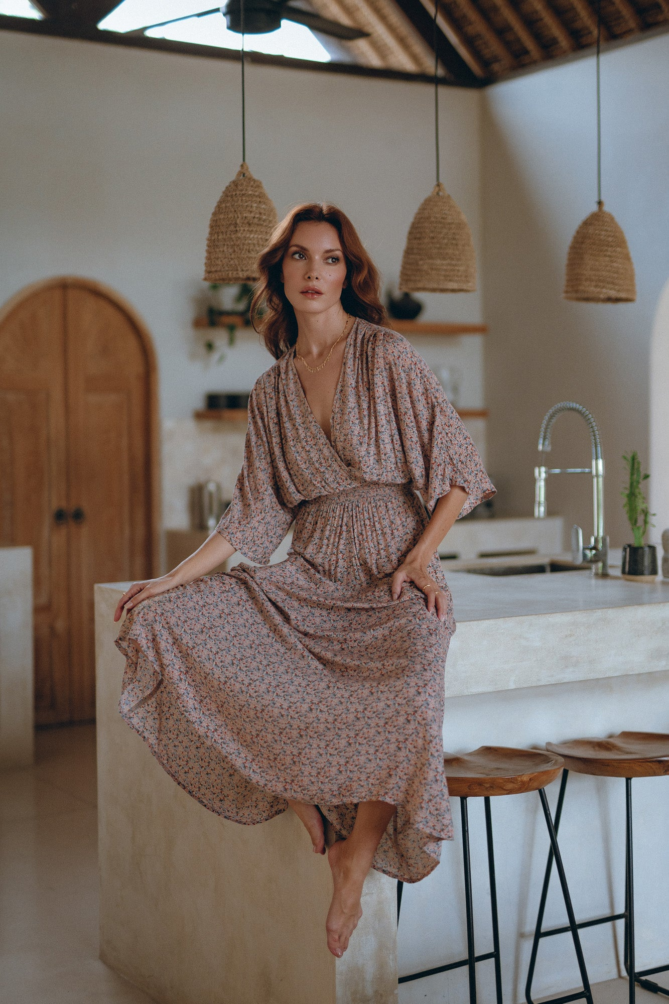 woman sitting in a kitchen of her summer house is wearing an elegant maxi dress