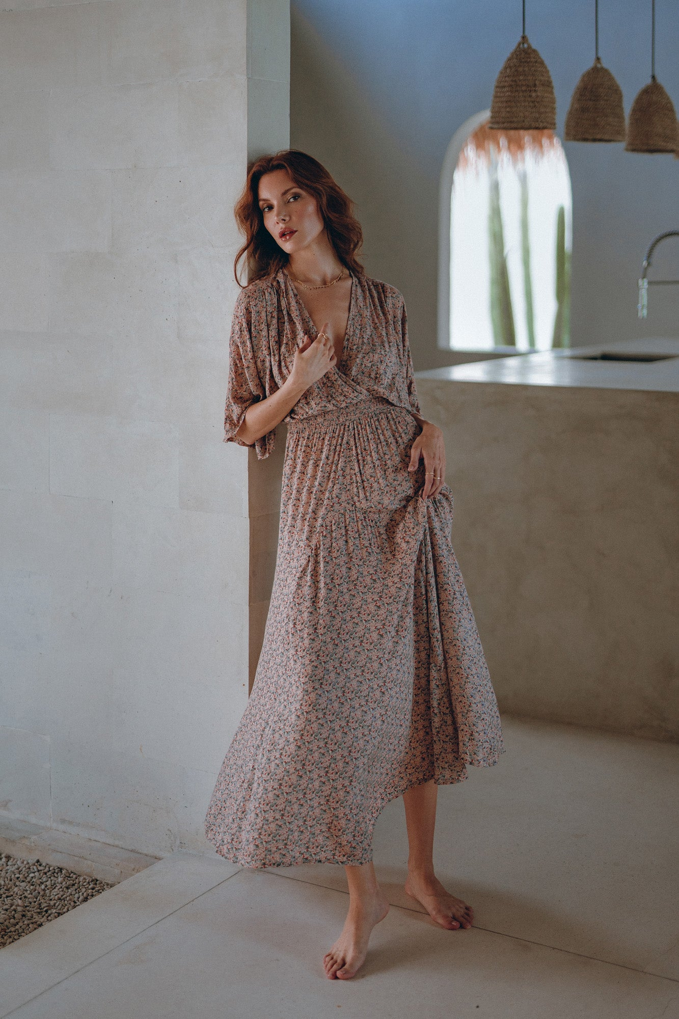 woman in her French riviera summer house is wearing a maxi dress with a botanical print