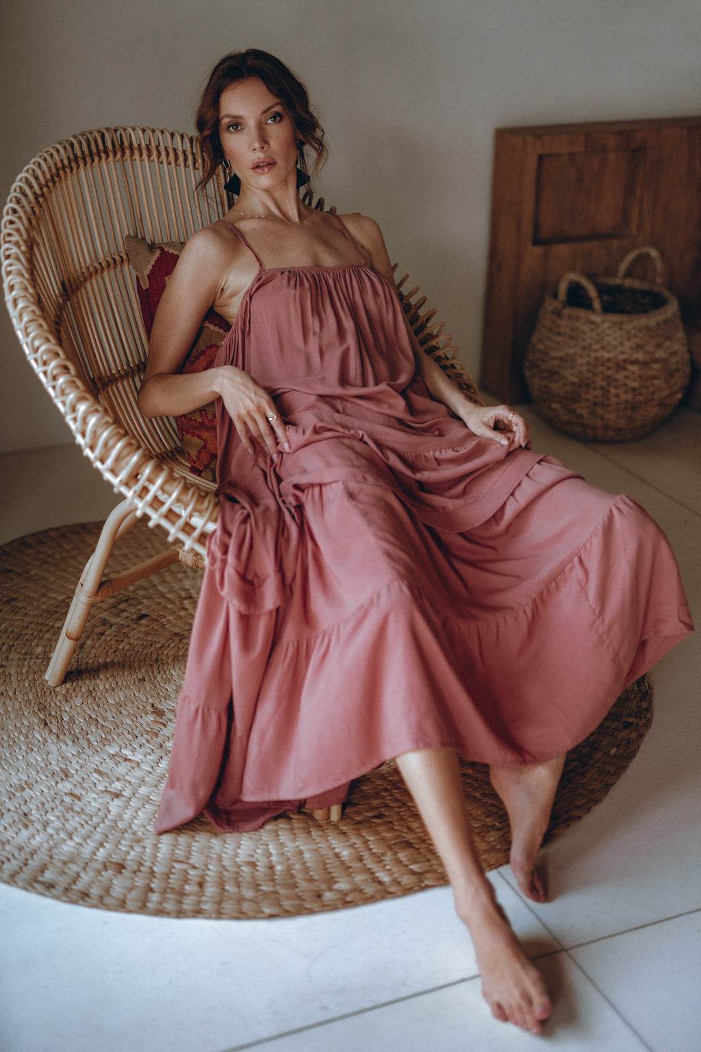 model in a pink maxi dress sitting in a chair