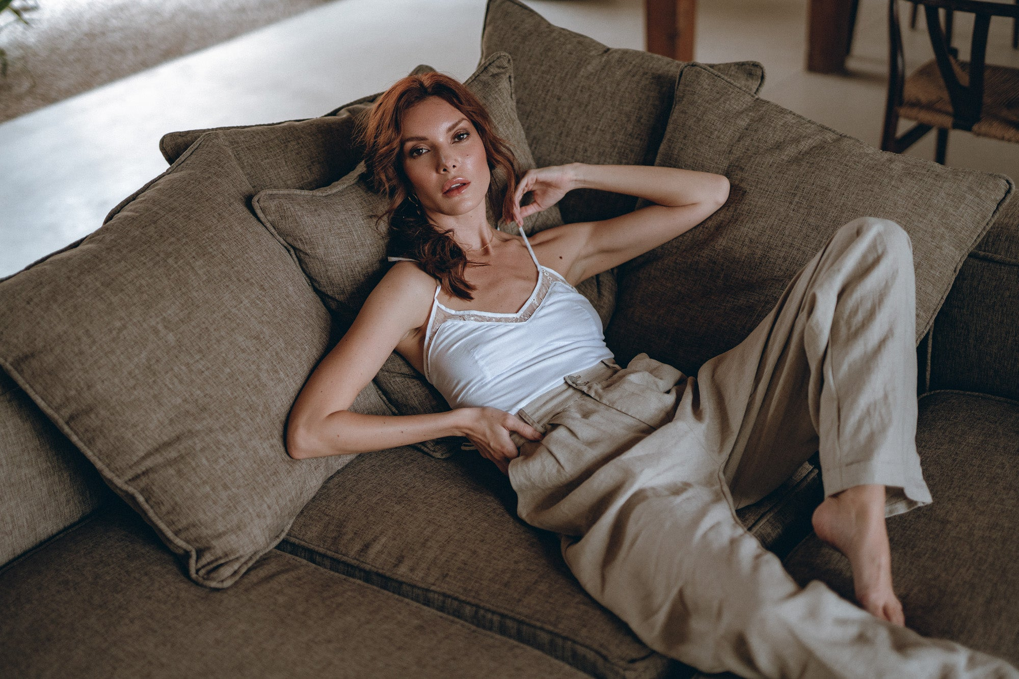 female model on a sofa is wearing grey linen pants and a white top