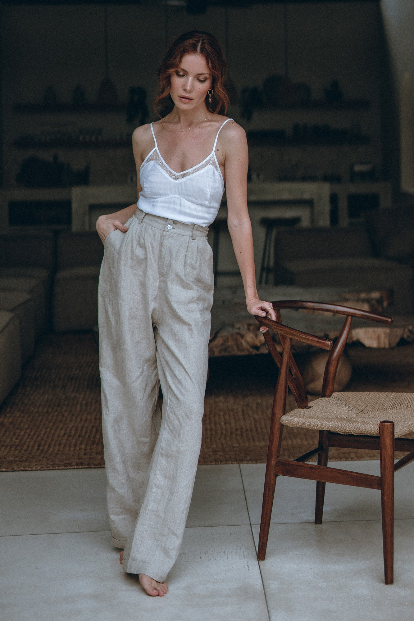 model in high-rise cut pants standing in an open kitchen in a house in Bali