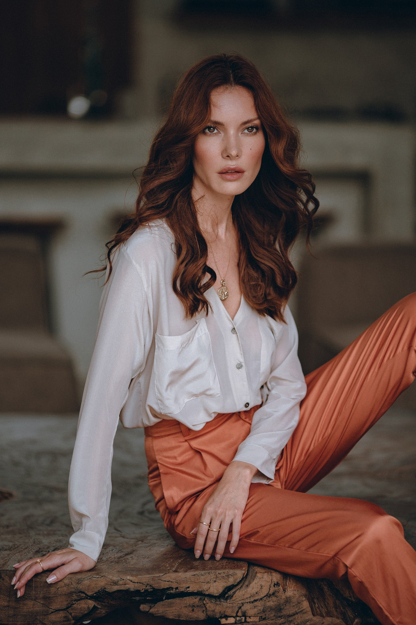 woman sitting on a table in a stunning silk shirt and satin pants