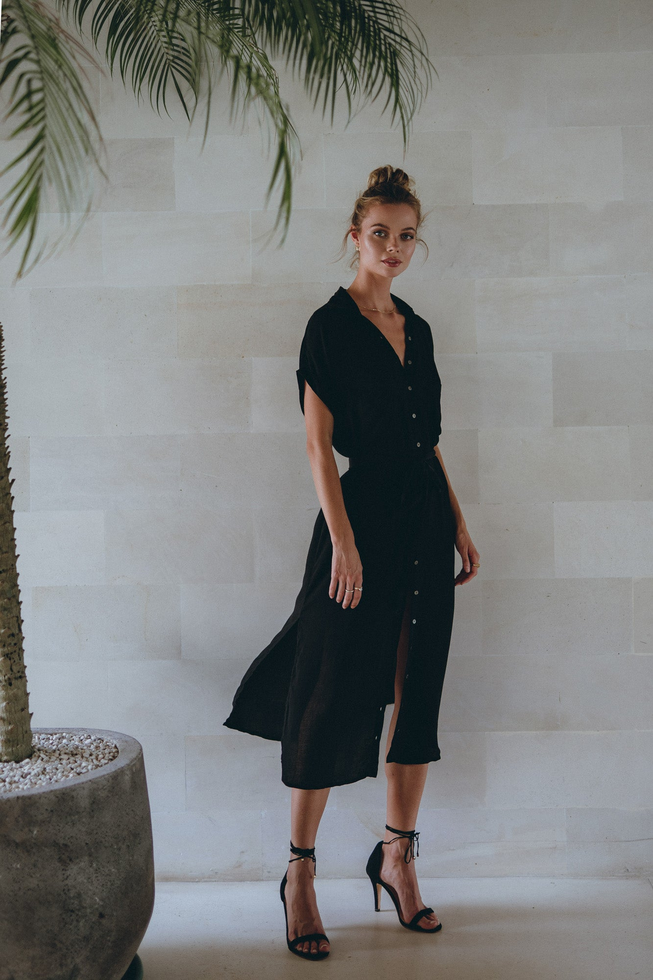 woman standing by a palm tree in a black midi dress from Pampelone