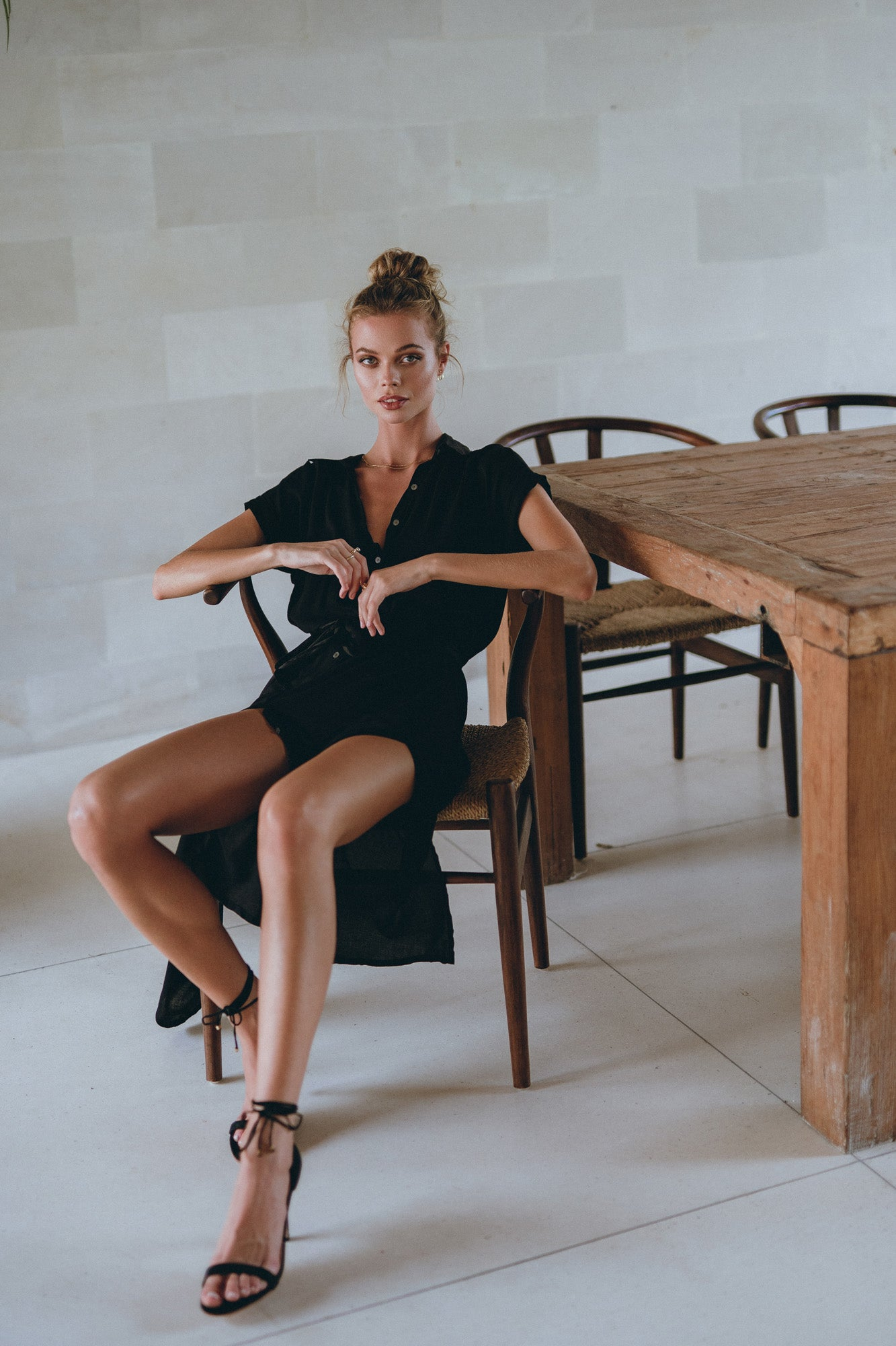 model sitting at the table dressed in a classic shirt dress, weraing black shoes