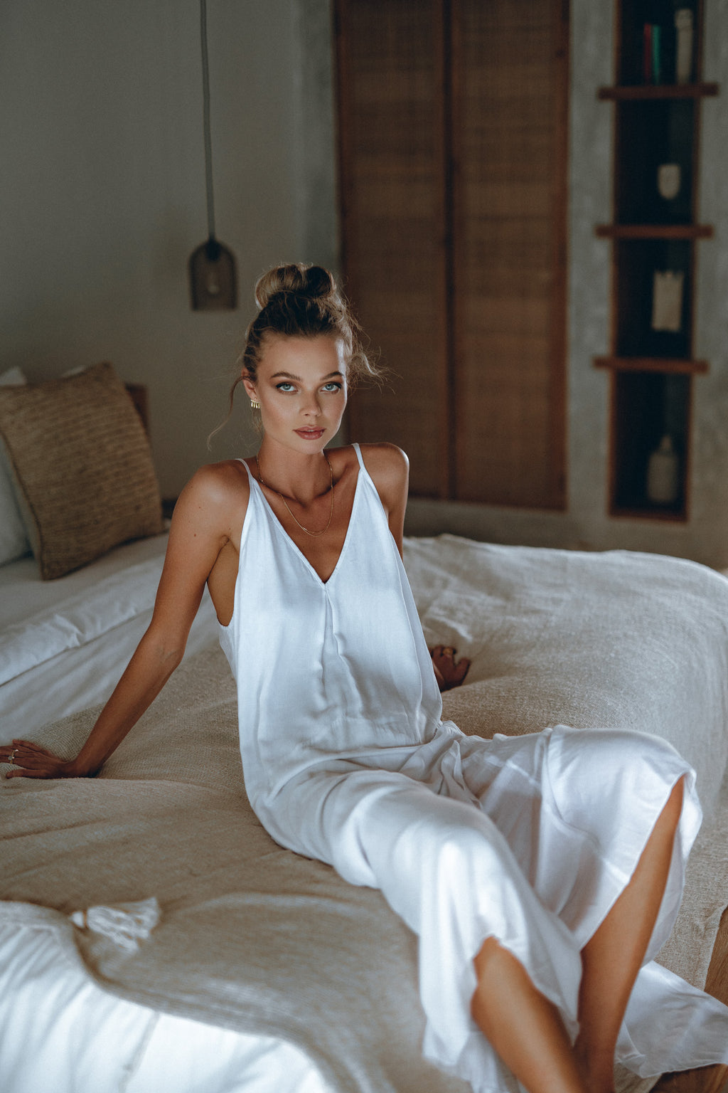 model sitting on bed dressed in a white flowy maxi dress