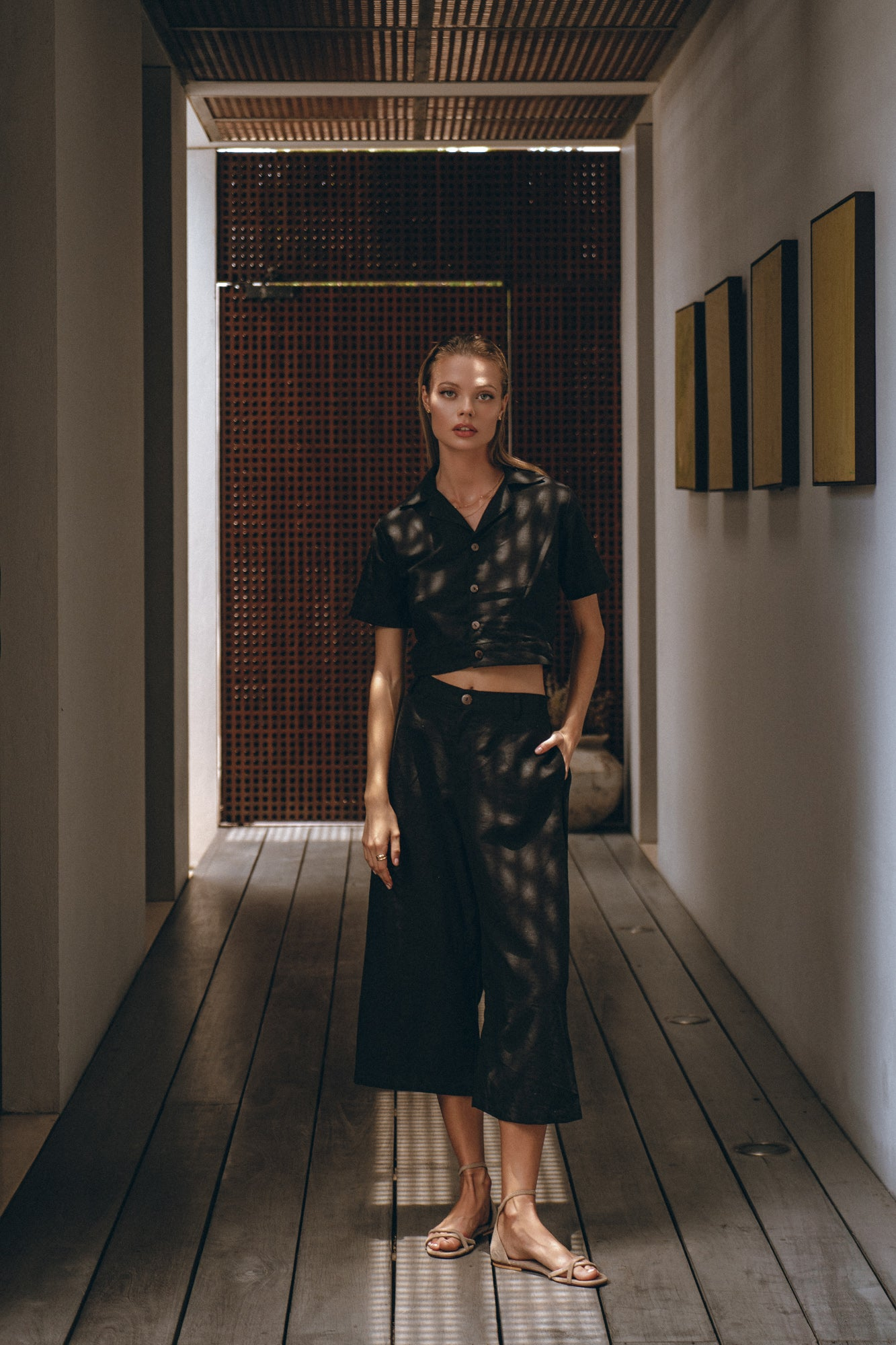 woman standing in a room, dressed in black fae linen pants and a black top
