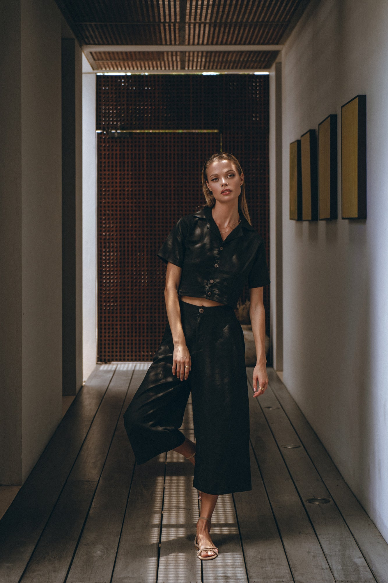 beautiful female model dressed in black linen pants and a black shirt