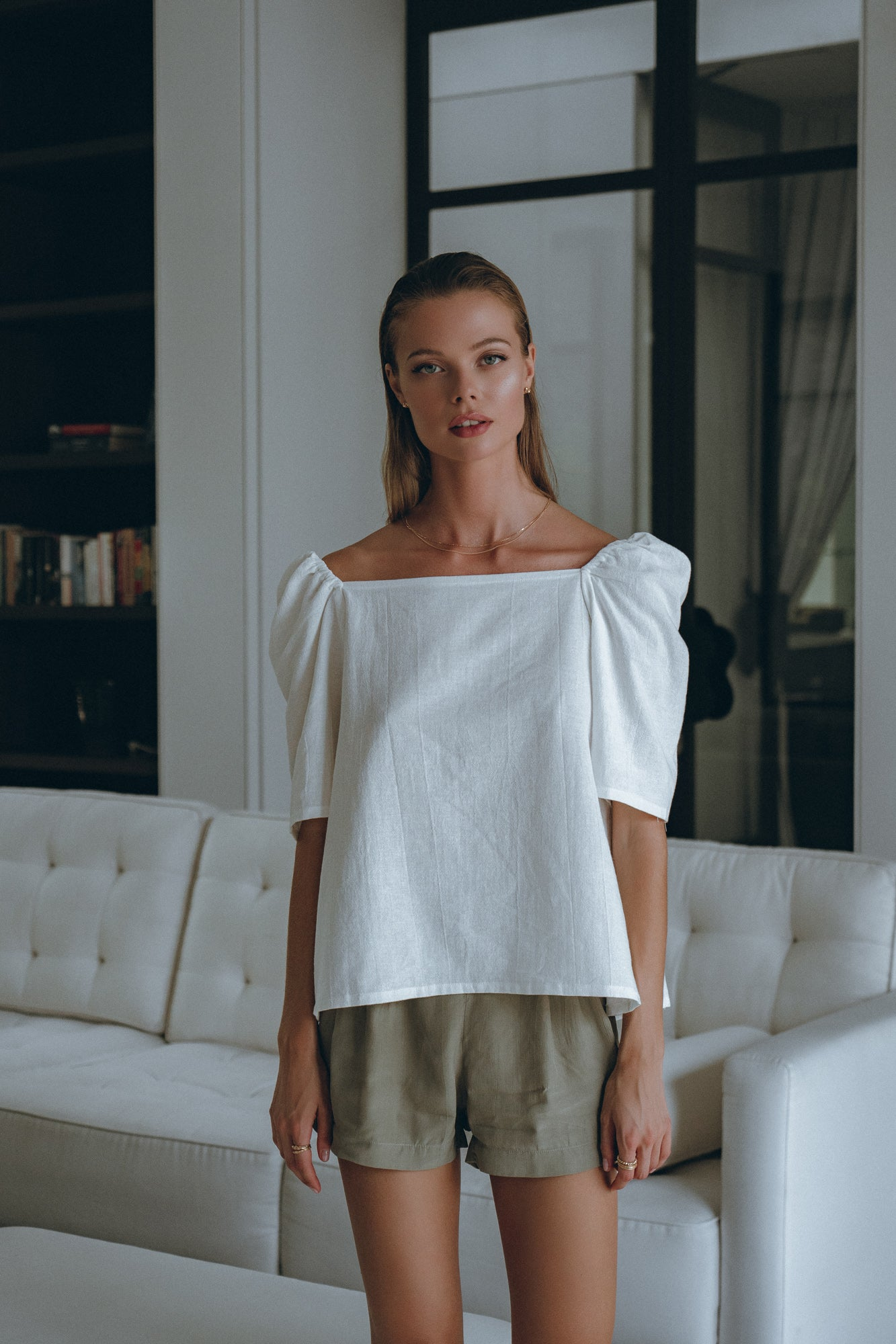 woman in her resort bungalow wearing reversible white shirt